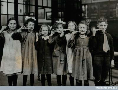 V0030839 Tooth-brush drill at school, England:ca 1920 Credit: Wellcome Library, London. Wellcome Images images@wellcome.ac.uk http://wellcomeimages.org Tooth-brush drill at school, England: children pose with tooth-brushes in mouth in a school building. Photograph, ca. 1920. 1920 Published:  -   Copyrighted work available under Creative Commons Attribution only licence CC BY 4.0 http://creativecommons.org/licenses/by/4.0/